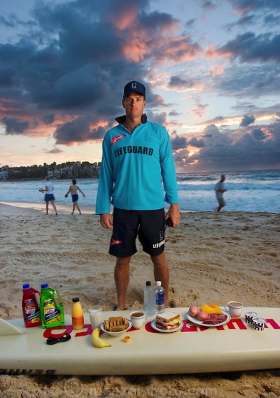 Bruce Hopkins, un salvavidas de Bondi Beach, con su comida típica de un día en Sydney, Nuevo Gales del Sur, Australia. El valor calórico de la comida en un día típico en el mes de febrero fue de 3,700 kcal. Él tiene 35 años de edad, mide 1.82 m y  pesa 81 kg. Hopkins come moderadamente, rara vez consume comida rápida y bebe alcohol sólo cuando él y su esposa van a cenar con amigos. Foto: Peter Menzel