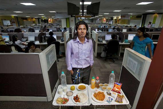 Shashi Kanth, un trabajador de call center con su comida diaria en su oficina en el centro de atención telefónica de AOL en Bangalore, India. Kanth mide 1.73 m y pesa 55 kg. Como muchos de los miles de trabajadores de call center en la India, se alimenta de comidas rápidas, golosinas y café para soportar las largas noches que pasa hablando con los occidentales sobre diversas cuestiones técnicas y problemas de facturación. Inicialmente se introdujo en el mundo del call center para pagar facturas médicas y escolares, pero después de dos años se encuentra todavía allí sin saber cuándo va a volver a sus estudios profesionales. Foto: Peter Menzel