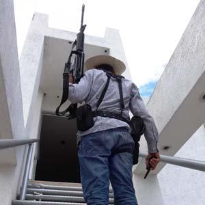 Un autodefensa sube al edificio contiguo al área de jaripeo. Foto Humberto Padgett SinEmbargo.