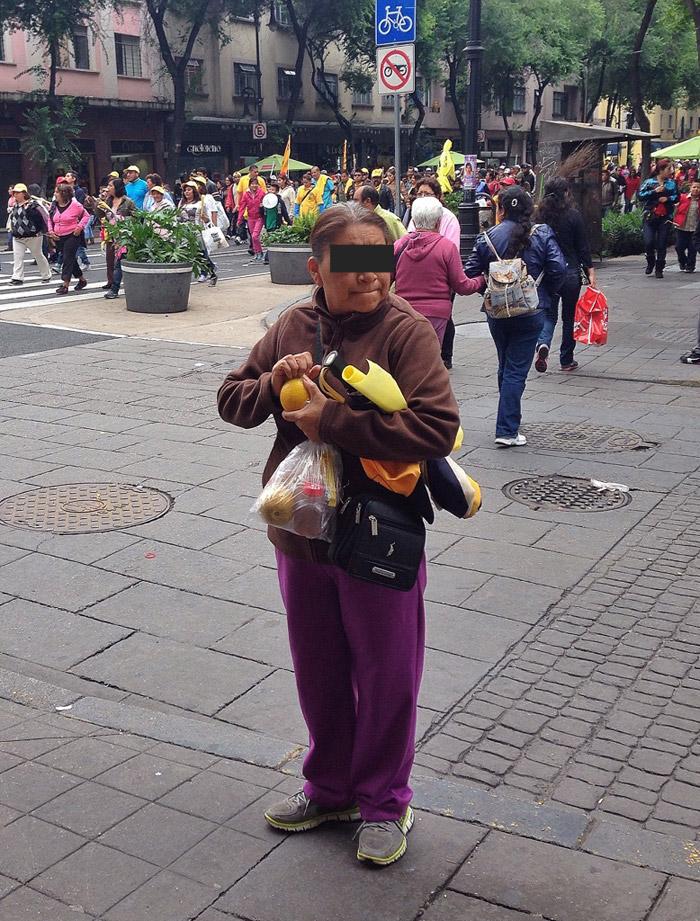 """Mujer de aspecto humilde encaminándose al Zócalo del DF con su """"lunch"""" en la mano. Foto: Francisco Cañedo, SinEmbargo"""