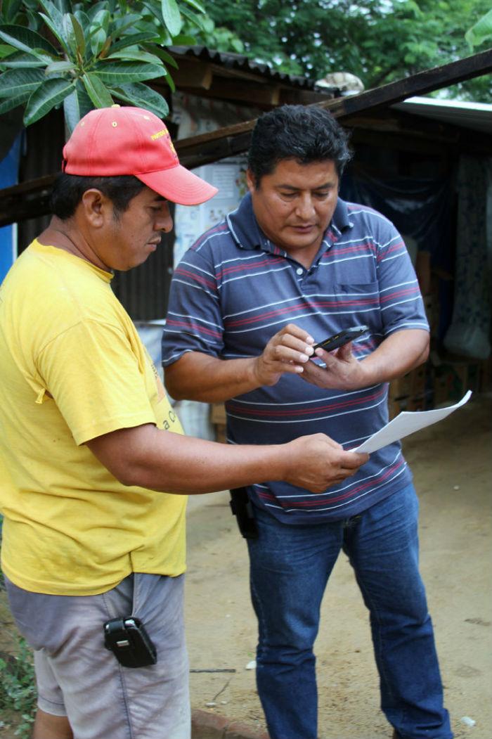 Miguel Ángel Jiménez Blanco, líder comunitario de UPOEG y activista político, trabaja con la policía de la comunidad local para recoger documentos de la presunta compra de votos y la coerción por los partidos políticos en junio de 2015. Foto: Kara Andrade