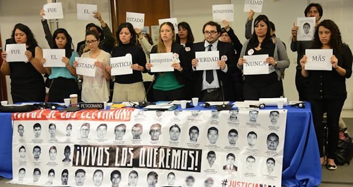 Manifestantes muestran imágenes de los 43 desaparecidos de Ayotzinapa en sesión de la CIDH celebrada en Washington. Foto: EFE