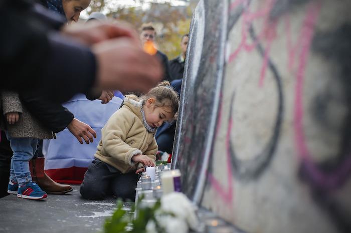Una niña enciende velas en altar a las víctimas de los atentados terroristas. Foto: Xinhua