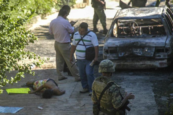 10 de noviembre de 2015. Un hombre asesinado en Acapulco, Guerrero, junto a un auto incendiado. Foto: Cuartoscuro