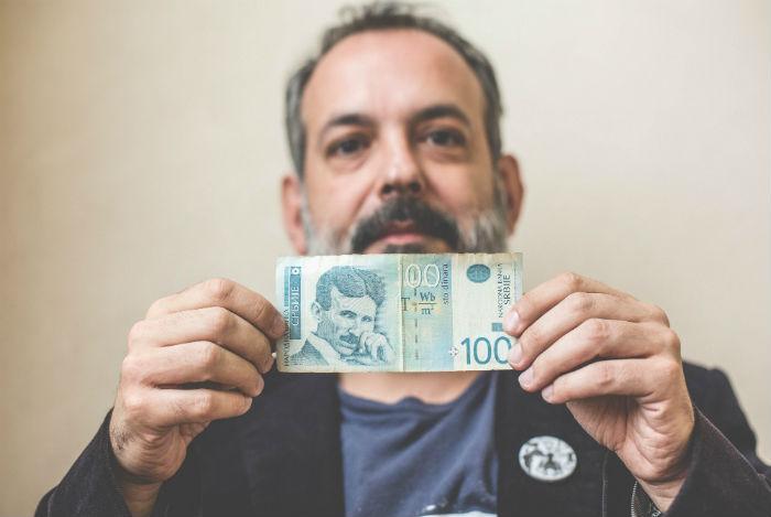 Miguel A.Delgado, autor de la novela de Tesla, con un billete que lleva el rostro del inventor. Foto: Francisco Cañedo, SinEmbargo