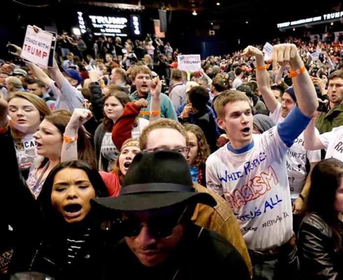 """Manifestantes gritan consignas contra Donald Trump en un acto en la Universidad de Chicago-Illinois, el 11 de marzo del 2016. En un ambiente caldeado por la candidatura de Trump, mucha gente está emitiendo un """"voto estratégico"""" en las primarias, no necesariamente por su candidato preferido, sino por el que más le conviene para conseguir su objetivo. Incluso si esto implica cambiar de bando y participar en la votación del otro partido. Foto: Charles Rex Arbogast, AP"""