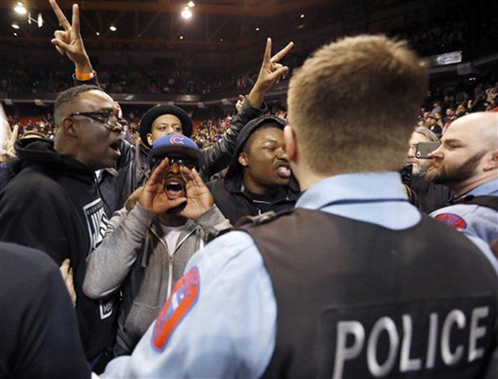 Manifestantes contrarios al precandidato republicano a la Casa Blanca Donald Trump gritan a sus partidarios tras el anuncio de la cancelación de un acto de campaña por razones de seguridad en la Universidad de Illinois-Chicago, el 11 de marzo de 2016, en Chicago. Foto: Charles Rex Arbogast, AP
