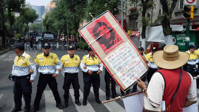 Elementos de seguridad vigilan la marcha de los maestros disidentes. Foto: Luis Barrón, SinEmbargo