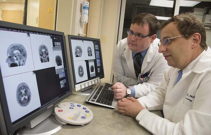 En esta foto proporcionada por la Universidad de Washington se observan el profesor asociado de neurología de la Escuela de Medicina de la universidad, Beau Ances, derecha, y Matthew Brier, estudiante de la universidad, mientras examinan una tomografía PET de un paciente con alzhéimer en St. Louis. Foto: AP