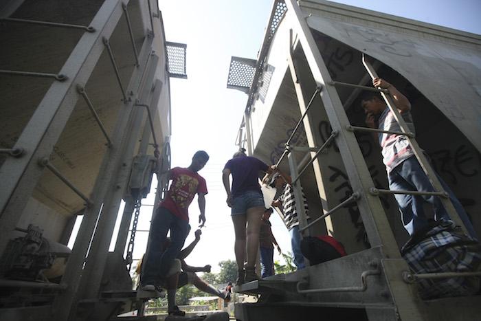 """Decenas de migrantes se suben a la """"bestia"""" en la estación ferroviaria de Tenosique, Tabasco. Foto: Cuartoscuro"""
