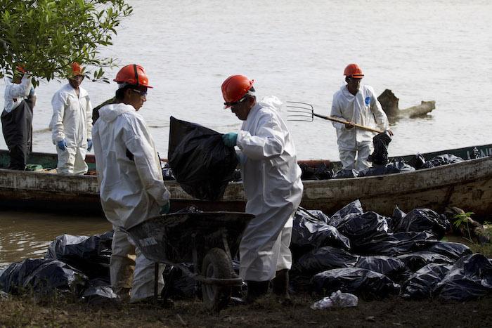 Trabajadores de Pemex recolectan el crudo después de la explosión de Coatzacoalcos. Foto: Cuartoscuro
