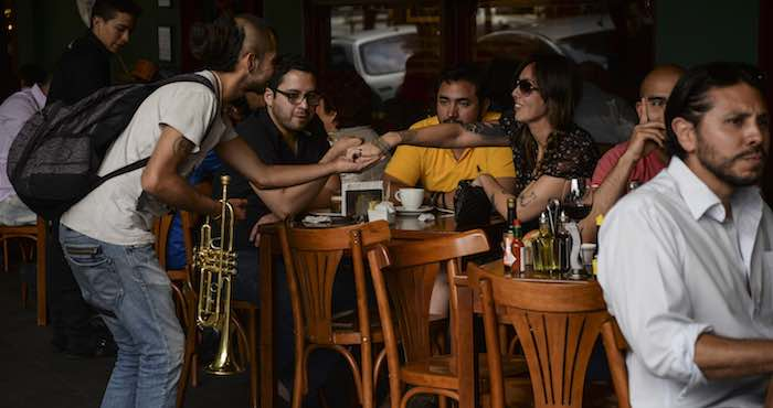 Un joven encuentra una buena oportunidad de ganar unas monedas, recorriendo los restaurantes de la colonia Roma con su trompeta. Foto: Cuartoscuro.