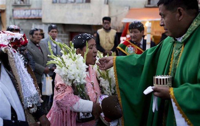 Indígena recibe la comunión en una misa comunitaria. Foto: AP/Juan Karita.