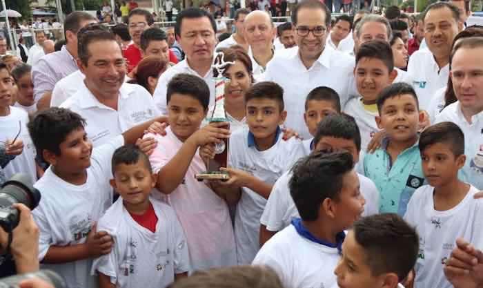 En la imagen, Miranda Nava (izq.), Miguel Ángel Osorio Chong (centro) y José Ignacio Peralta (der.) posan junto a un grupo de menores en la Unidad Deportiva de Colima. Foto: Twitter [@LuisEMirandaN].