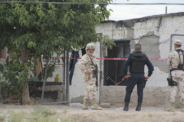 Un militar y un policía afuera de una casa en Ciudad Juárez. Foto: Cuartoscuro.