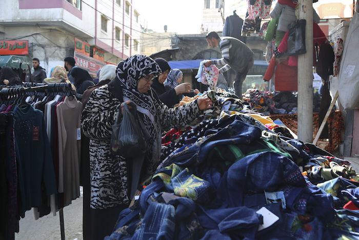 """GRA143. GAZA, 07/01/2017.- La pobreza, el desempleo y los diez años de férreo bloqueo israelí a Gaza han hecho proliferar los mercadillos y tiendas de ropa de segunda mano o """"ropa de batalla"""", como se conoce aquí esta opción, antes denostada y ahora cada vez más demandada. EFE/Mohamed Al Madhoun"""