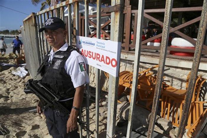 Un policía monta guardia frente a la salida del club nocturno Blue Parrot en Playa del Carmen. Foto: AP