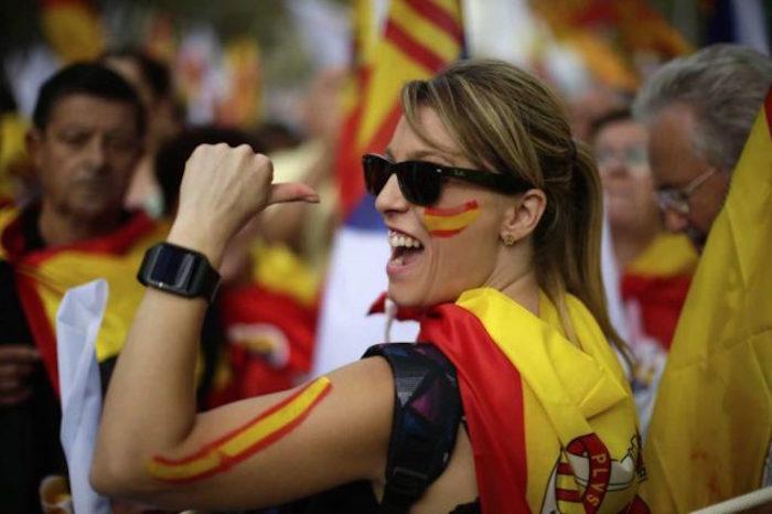 """Una mujer envuelta en la bandera española desfila en el """"Día de la Hispanidad"""" en Barcelona España"""
