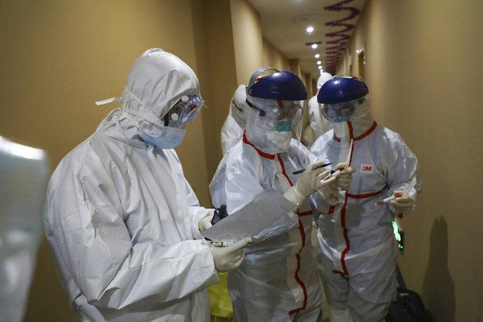 Un trabajador médico escribe en un tubo tras recoger una muestra de un paciente en un hotel utilizado para colocar a personas en cuarentena en Wuhan. Foto: Chinatopix vía AP