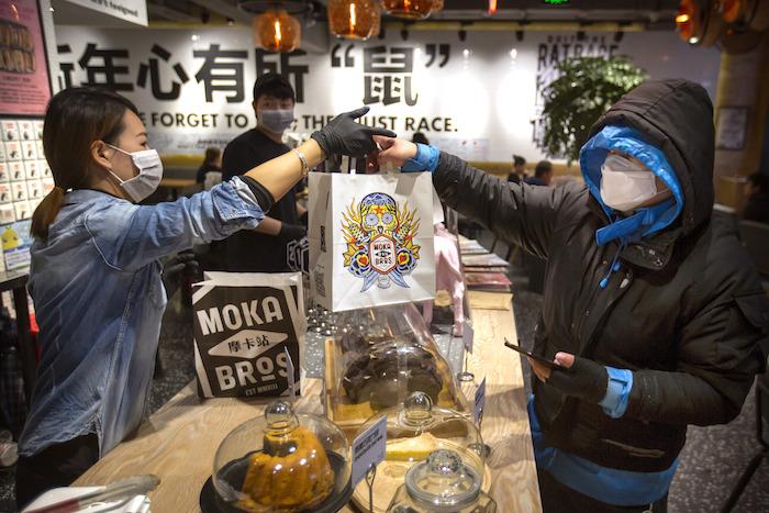 El gerente Chen Tiantian, izquierda, entrega una orden a un repartidor en la cafetería Moka Bros de Beijing, el viernes 14 de febrero de 2020. Como muchos negocios en China, Moka Bros pasa apuros para enfrentar las secuelas del brote de coronavirus que ha infectado a decenas de miles de personas en el mundo. Foto: Mark Schiefelbein, AP