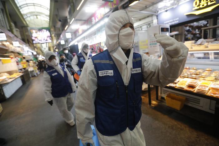 Trabajadores con equipo de protección llegan para rociar desinfectante como precaución contra el coronavirus en un mercado en Seúl, Corea del Sur, el lunes 24 de febrero de 2020. Foto: Ahn Young-joon, AP