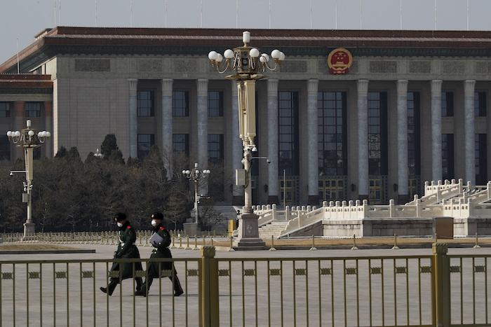 En esta imagen del domingo 23 de febrero de 2020, policías paramilitares con mascarillas de protección caminan por la vacía plaza de Tiananmen, con el Gran Salón del Pueblo al fondo, en Beijing, China. Foto: Andy Wong, AP