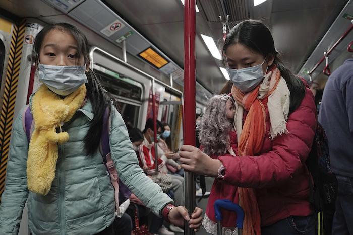 Dos niñas viajan en el metro de Hong Kong el sábado 1 de febrero de 2020, durante la emergencia por el coronavirus. Foto: AP
