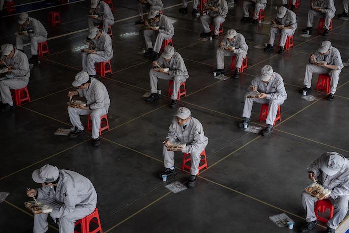 Trabajadores de una fábrica de Wuhan, en la provincia china de Hubei donde se localizó el epicentro de la pandemia de coronavirus, hacen su descanso para el almuerzo guardando el metro y medio de distancia de seguridad establecido para evitar el contagio de la enfermedad. Foto: EFE/EPA/Yi Xin