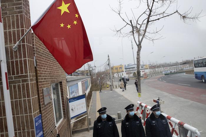 Guardias de seguridad con máscaras faciales para protegerse del coronavirus vigilan la entrada de la planta eléctrica Huadian Beiran Corporation en Beijing, el jueves 27 de febrero de 2020. Foto: Ng Han Guan, AP