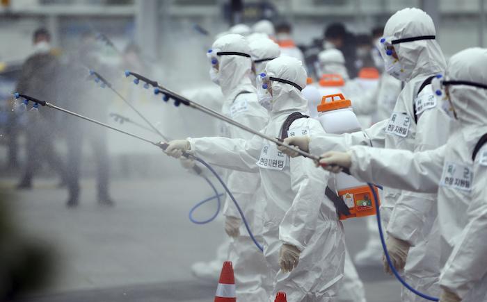 Soldados del ejército surcoreano, portando trajes protectores, rocían desinfectante para prevenir el contagio con el nuevo coronavirus en la estación de trenes de Dongdaegu en Daegu, Corea del Sur, el sábado 29 de febrero de 2020. Foto: Kim Hyun-tai/Yonhap vía AP