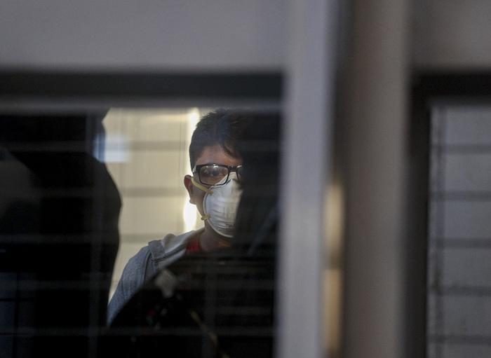 Un pasajero con una mascarilla usa un elevador antes de abordar un vuelo en el Aeropuerto Internacional Arturo Benítez en Santiago, Chile, 3 de marzo de 2020. Foto: Esteban Félix, AP