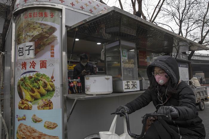 Una mujer con cubrebocas a bordo de una bicicleta pasa frente a un local de comida en un distrito comercial del centro de Beijing, el lunes 9 de marzo de 2020. Foto: Ng Han Guan, AP