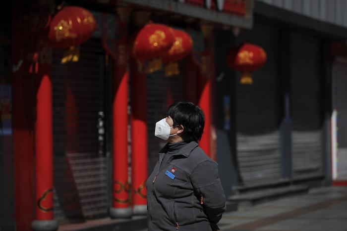 Una mujer que porta una mascarilla observa unos negocios cerrados en el distrito comercial de Wangfujing, en Beijing, el martes 10 de marzo de 2020. Foto: Andy Wong, AP