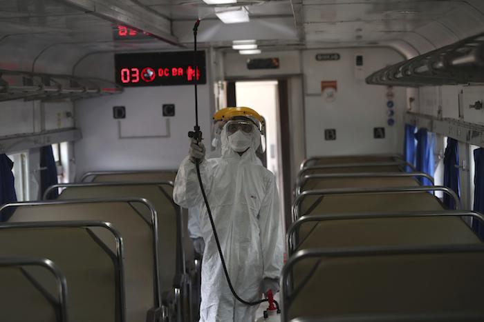 Un empleado con equipo de protección rocía desinfectante en un tren para combatir un brote de coronavirus en la estación de tren de Senen, en Yakarta, Indonesia, el domingo 15 de marzo de 2020. Foto: Tatan Syuflana, AP