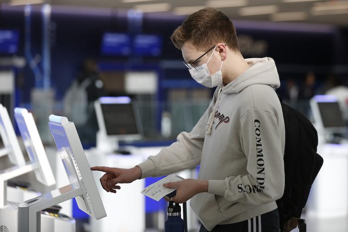 El estudiante universitario en Nueva York Hector Medrano, de Los Ángeles, factura en su vuelo con una pantalla táctil, el sábado 14 de marzo de 2020 en la terminal de jetBlue, en el aeropuerto John F. Kennedy International en Nueva York. Foto: Kathy Willens, AP