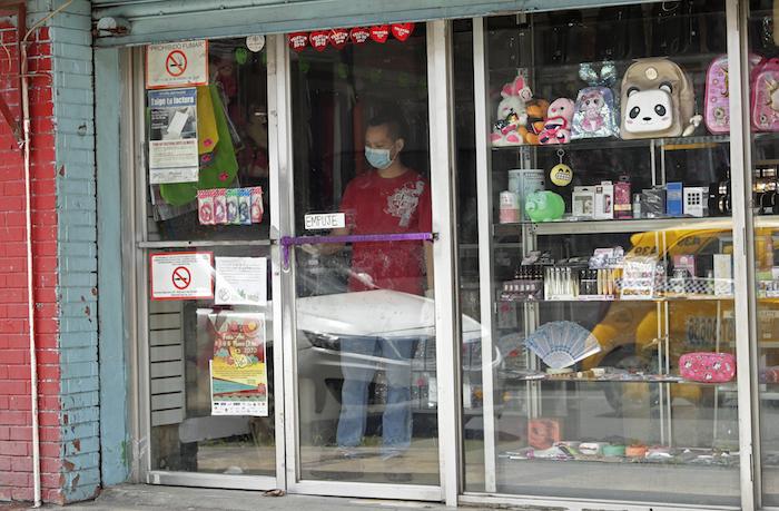 """Un hombre con una mascarilla para protegerse de un posible contagio por coronavirus limpia la ventana de una tienda en el barrio """"China Town"""" en la Ciudad de Panamá, el jueves 12 de marzo de 2020. Foto: Arnulfo Franco, AP"""