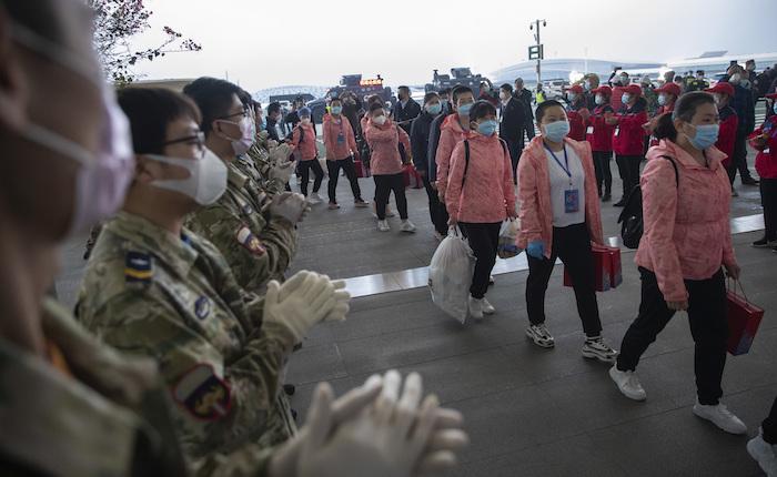 En esta fotografía del 18 de marzo de 2020 difundida por la Agencia de Noticias Xinhua de China, personas aplauden a personal médico que se marcha al momento en el que ingresa en el aeropuerto internacional Wuhan Tianhe, en Wuhan, que fue el epicentro del coronavirus, en la provincia de Hubei, centro de China. Foto: Ke Hao/Xinhua vía AP