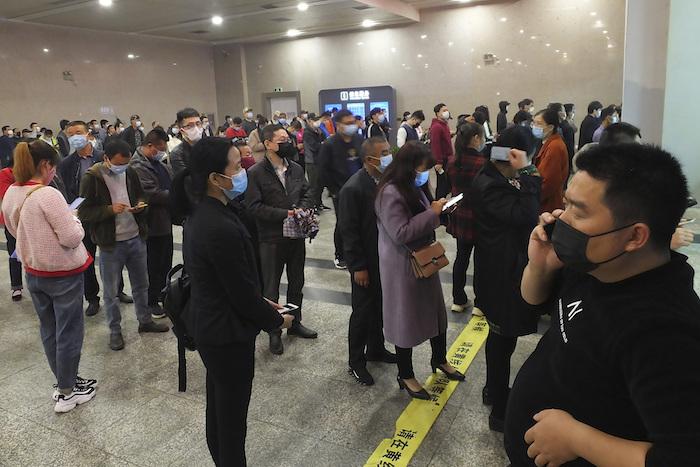 Viajeros hacen fila para comprar boletos de tren en Yichang, provincia de Hubei, China, miércoles 25 de marzo de 2020. Foto: Chinatopix vía AP