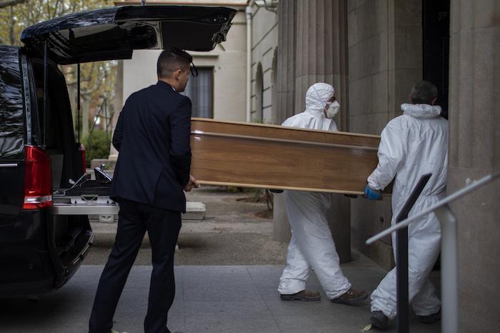 Empleados de una funeraria trasladan un ataúd para un entierro en un cementerio en Barcelona durante el brote del coronavirus en España, el viernes 27 de marzo de 2020. Foto: Emilio Morenatti, AP