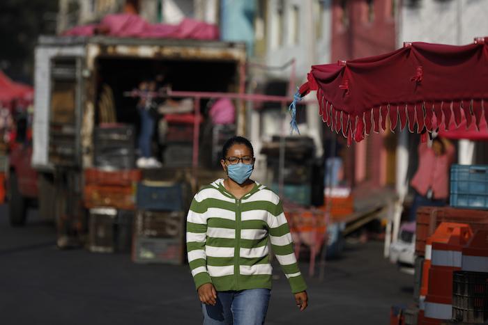 Una mujer con mascarilla camina entre los puestos de un mercado ambulante en la Ciudad de México, el domingo 29 de marzo de 2020. Foto: Rebecca Blackwell, AP