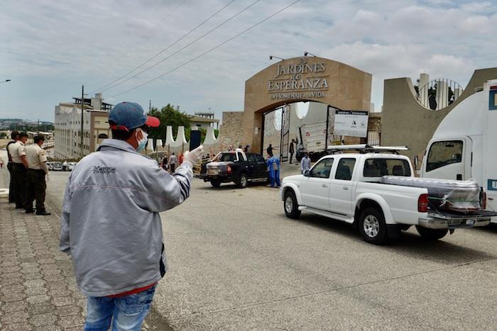 Vista este miércoles de dos vehículos que transportan los féretros de dos fallecidos por COVID-19, a su llegada a un cementerio de Guayaquil (Ecuador). Foto: Marcos Pin, EFE