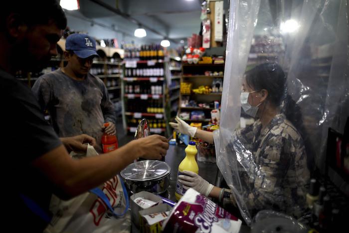 Una vendedora de supermercado espera a un cliente detrás de una cortina de plástico como precaución contra el nuevo coronavirus en Buenos Aires, Argetina, el lunes 16 de marzo de 2020. Foto: Natacha Pisarenko, AP
