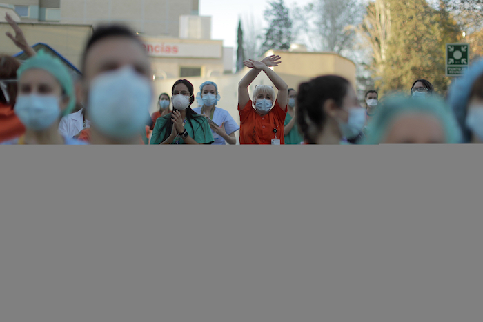 Trabajadores sanitarios aplauden a la gente que, desde sus casas, muestra su apoyo al personal que trabajaba para contener el brote de coronavirus, en el hospital Gregorio Marañón, en Madrid, el 1 de abril de 2020. Foto: Manu Fernández, AP