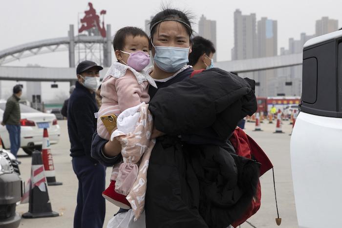 En esta imagen, tomada el 2 de abril de 2020, una mujer con una niña en brazos se aleja de una carretera en la frontera de la ciudad de Wuhan, en la provincia de Hubei, en el centro de China. Foto: Ng Han Guan, AP