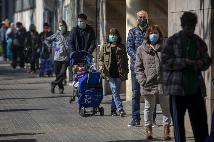 Personas con mascarillas se forman para comprar provisiones en una tienda durante el brote del coronavirus en Barcelona, España, el sábado 4 de abril de 2020. Foto: Emilio Morenatti, AP
