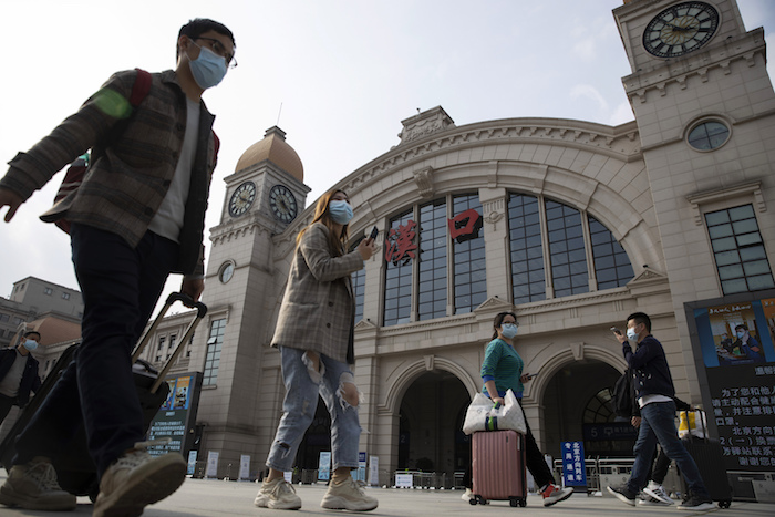 Viajeros con maletas caminan frente a la estación ferroviaria de Hankou cuando se apresta a reanudar el tráfico desde Wuhan, China, hacia afuera de la ciudad, martes 7 de abril de 2020. Foto: Ng Han Guan, AP