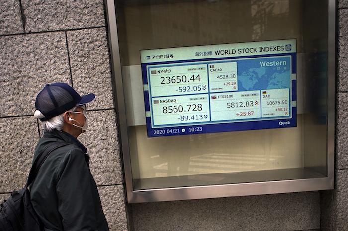 Un hombre camina frente a una cartelera con datos financieros en Tokio, 21 de abril del 2020.