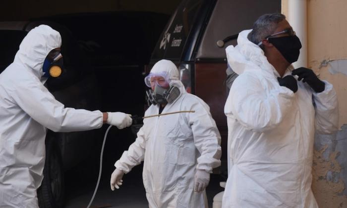 Entre los mismos compañeros se sanitizan los trajes de protección. Foto: Rey R. Jauregui, La Verdad de Juárez