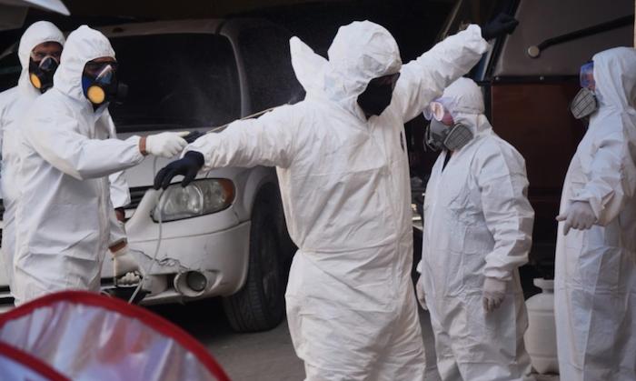 El personal que tiene contacto con los cadáveres sanitiza sus trajes de protección. Foto: Rey R. Jauregui, La Verdad de Juárez