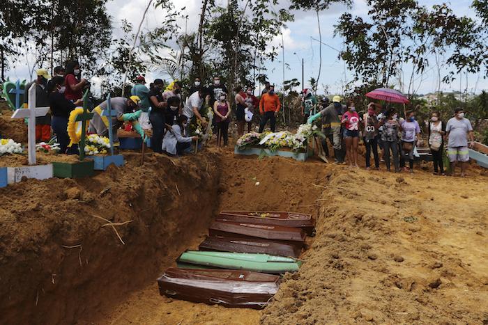 En esta imagen, tomada el 21 de abril de 2020, familiares asisten a un entierro múltiple en el cementerio Nossa Senhora Aparecida, en Manaos, en el estado de Amazonas, Brasil. El cementerio realiza entierros en fosas comunes ante el elevado número de decesos por la COVID-19, dijo un funcionario.
